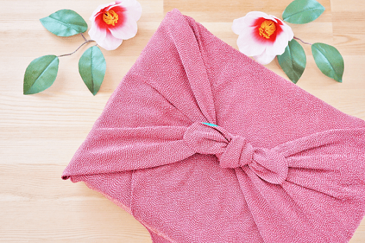 ピンクの風呂敷に包まれた贈り物と白い椿