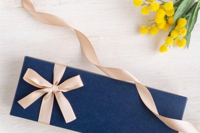 青いギフトボックスとリボンとミモザの花